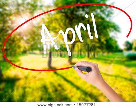 Woman Hand Writing  April  With A Marker Over Transparent Board
