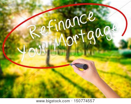 Woman Hand Writing Refinance Your Mortgage With A Marker Over Transparent Board