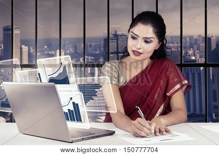 Indian businesswoman working in the office with virtual financial chart and writing on the paperwork