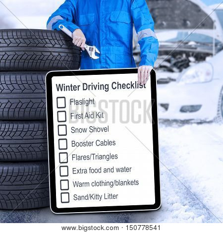 Male mechanic leaning on a stack of tires while holding a winter driving tips and a wrench shot outdoors