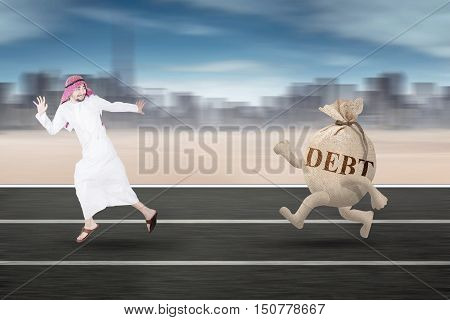 Photo of a middle eastern entrepreneur running away from a money bag with debt words on the street