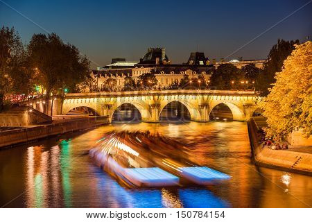 Pont Neuf bridge and Seine River at twilight with city lights and passing tourist boat in summer. Ile de la Cite, 1st and 6th Arrondissement, Paris, France