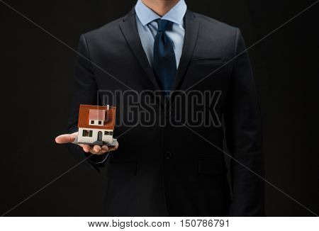 architecture, building, construction, real estate and property concept - close up of businessman or real estate agent holding house or home model on palm over black background