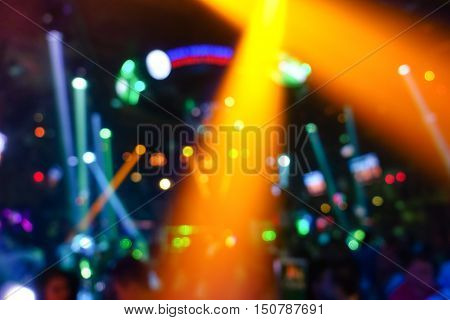 Defocused background with abstract bokeh of laser show in modern disco party night club - Nightlife concept with music and entertainment - Image with enhanced colored halos and vivid bright lights