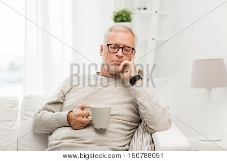 old age, drink and people concept - senior man with cup of tea at home
