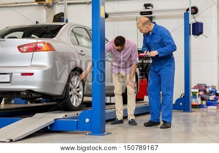 auto service, repair, maintenance and people concept - mechanic with clipboard and man or owner showing wheel at car shop