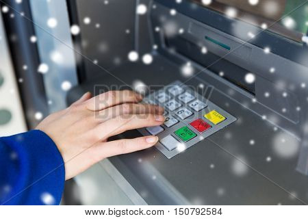 finance, technology, money, winter and people concept - close up of hand entering pin code at cash machine over snow