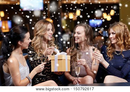 celebration, friends, new year, christmas and winter holidays concept - happy women with champagne glasses and gift box at bachelorette or birthday party at night club over snow
