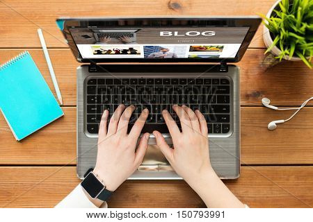 blogging, business, people and technology concept - close up of woman or student typing on laptop computer with blog page on screen, notebook and earphones on wooden table