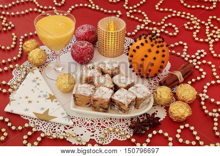 Christmas still life with stollen cake bites on a heart shaped plate, eggnog, gold foil wrapped chocolates, spices, candle, orange pomander and gold bead decorations on a red background.