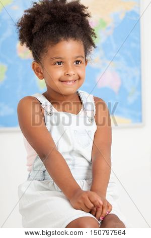 Cute preschool girl with world map at the class room