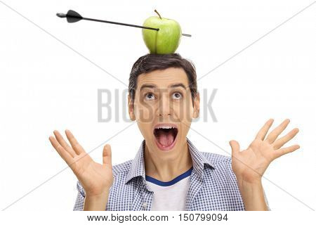 Scared guy looking at an apple pierced by an arrow on his head isolated on white background