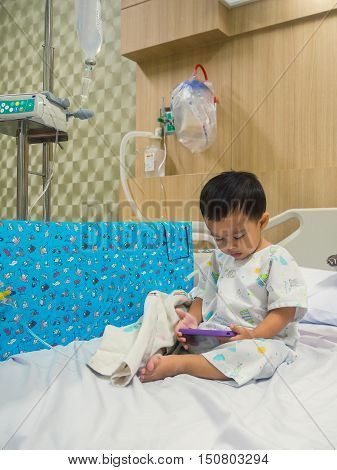 Illness asian boy sitting on sickbed in hospital with infusion pump intravenous IV drip.