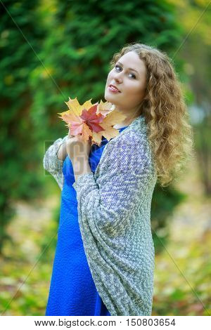 beautiful young woman holding yellow leaves in the autumn park outdoor
