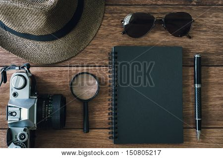 Black notebook with copyspace and retro camera on wooden background Top view