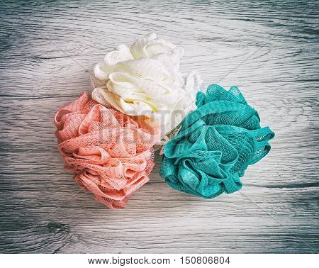 Pink white and turquoise washcloths on the wooden background. Body care. Toileting theme. Product photo.