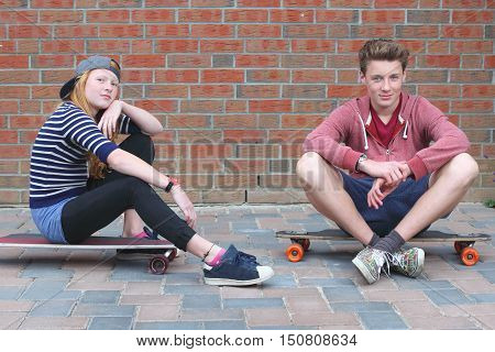 Portrait of two cool young teenagers outdoors with their skateboards