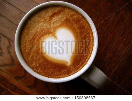 Heart latte art coffee on wooden background