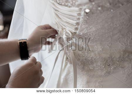 Closeup Image Of Wedding Preparations. Bridesmaid Is Helping Put Bride Elegant Luxury Dress.