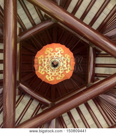 Orange chinese lampion with golden ornaments under wooden roof