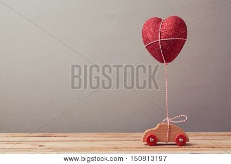 Heart shape balloon and car toy on wooden table. Valentine's day concept.