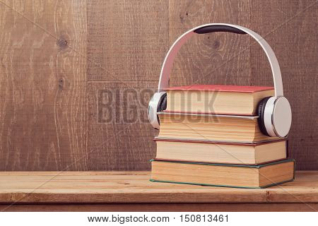 Audio books concept with stack of old book and headphones on wooden table