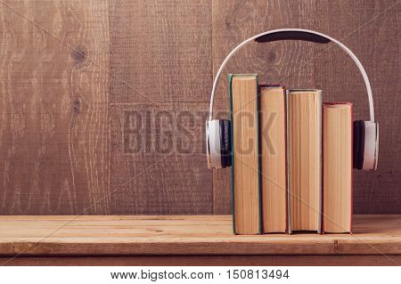 Audio books concept with old books and headphones over wooden background