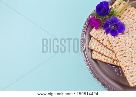 Passover background with matzah seder plate and spring flower. Flat lay view from above