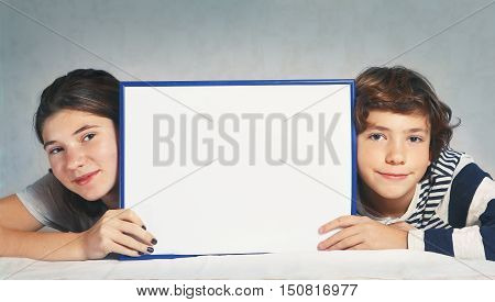 siblings teen boy and girl hold blank paper rectangular frame close up photo