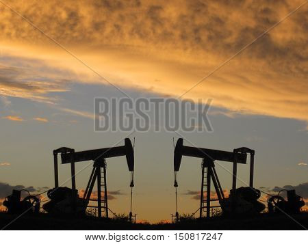 Two small pumper jacks during an orange sunset