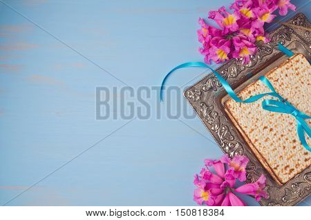 Passover spring holiday background with matzoh and flowers. View from above