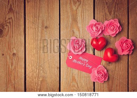 Happy Mother's day background with heart shapes and roses on wooden board