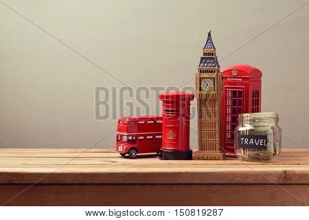 Travel to Great Britain concept with souvenirs and money box jar. Planning summer vacation money budget trip concept.