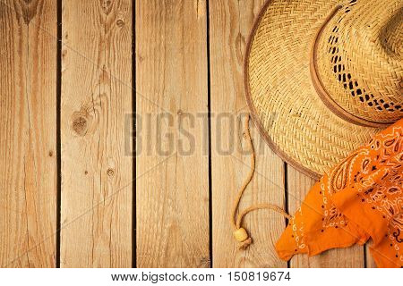 Rustic wooden background with cowboy hat and bandanna. View from above
