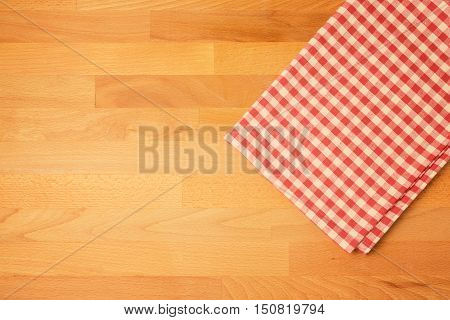 Checked tablecloth on wooden kitchen counter. View from above