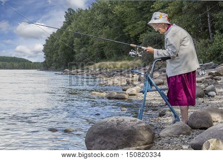 horizontal image of an elderly senior woman with a walker fishing at the edge of the lake with trees and rocks lining the shoreline in the summer time