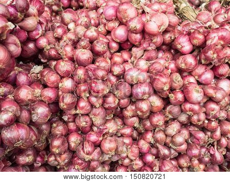 Pile of red onions for sale in market.