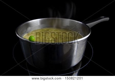 Fresh green pea on a pot with steaming vegetable soup on an induction heater black background concept for vitamin-preserving cooking or metaphor for a dangerous dare selected focus narrow depth of field