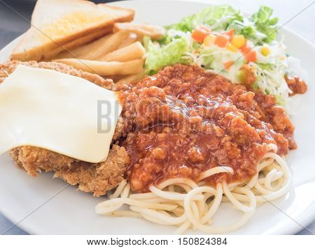 Pork steak with bread and Spaghetti on a white dish.