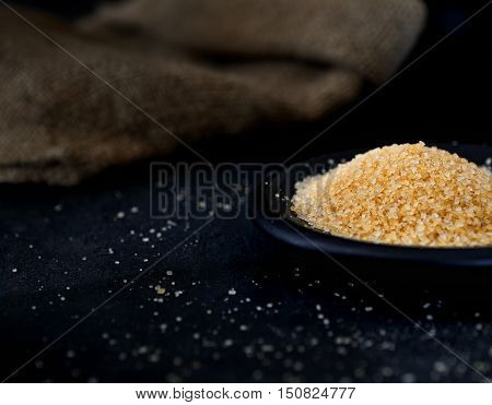 Crystals of brown sugar on a saucer on a dark background