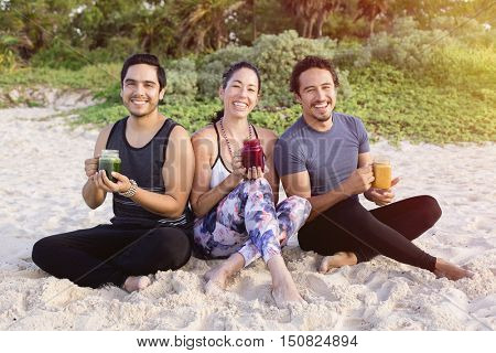 Three yogis having a smoothie on the beach