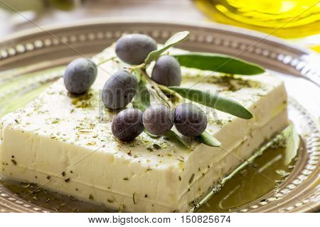 Feta cheese in the plate and branch of olives on the top. Feta cheese and olive branch. Horizontal. Daylight. Close.