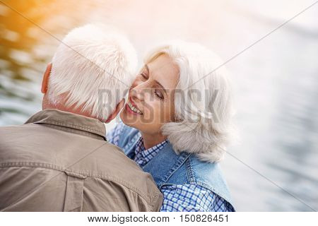 I love you. Happy old woman is whispering while sharing her feeling s with husband. She is sitting near lake and smiling