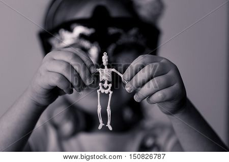 A skeleton, a girl, and a candle. Black and white.
