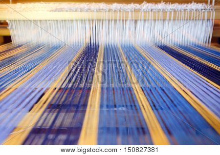 An home made loom colorful threads on a machine.