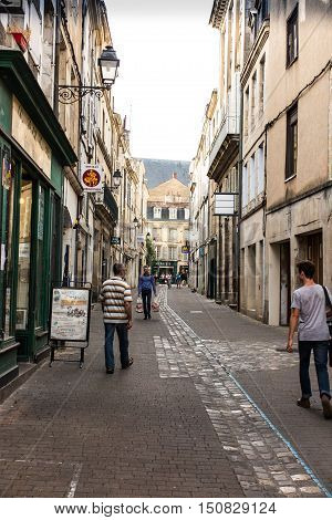 Poitiers France - September 12 2016: Alley in the old town of Poitiers France and hurry unidentified people passing in a hurry next.
