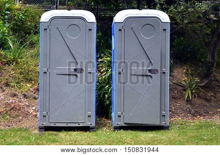 Two portable bathrooms in the field of a camp ground.