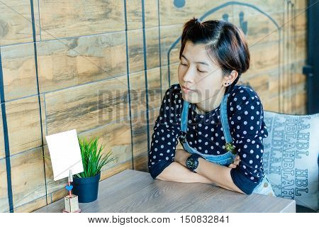 Beautiful Asian woman being lonely sad between Waiting for coffee in Coffee shop