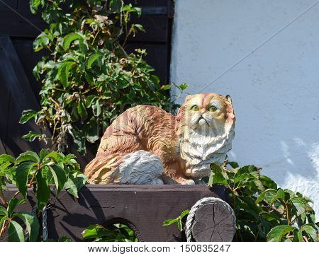 Toy Cat On The Fence. Statuette Of A Cat In Plaster And Plastic On The Fence
