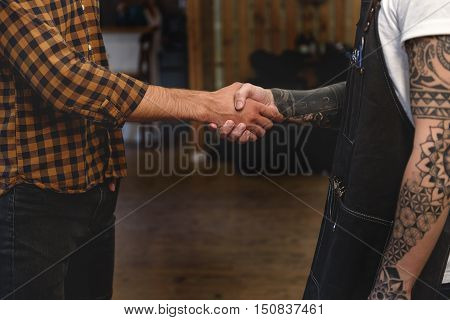 close up of hairstylist shaking hands with client while standing at barbershop
